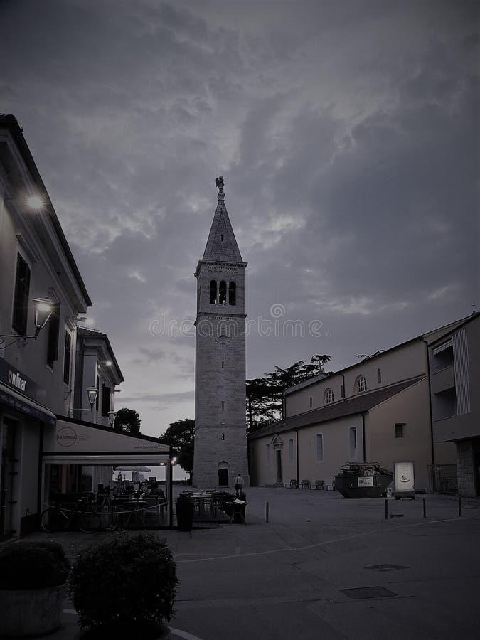 Παλαιά πόλη Istrian Novigrad, Κροατία Μια όμορφη εκκλησία με έναν υψηλό κομψό πύργο κουδουνιών, αλέες πετρών και ένα παλαιό μεσογ στοκ φωτογραφία