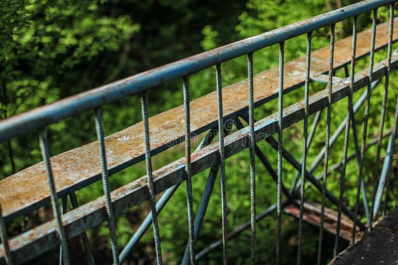 Παλαιά ράγα φρουράς μετάλλων της γέφυρας, με το θολωμένο πράσινο δάσος στην ΤΣΕ στοκ φωτογραφία με δικαίωμα ελεύθερης χρήσης