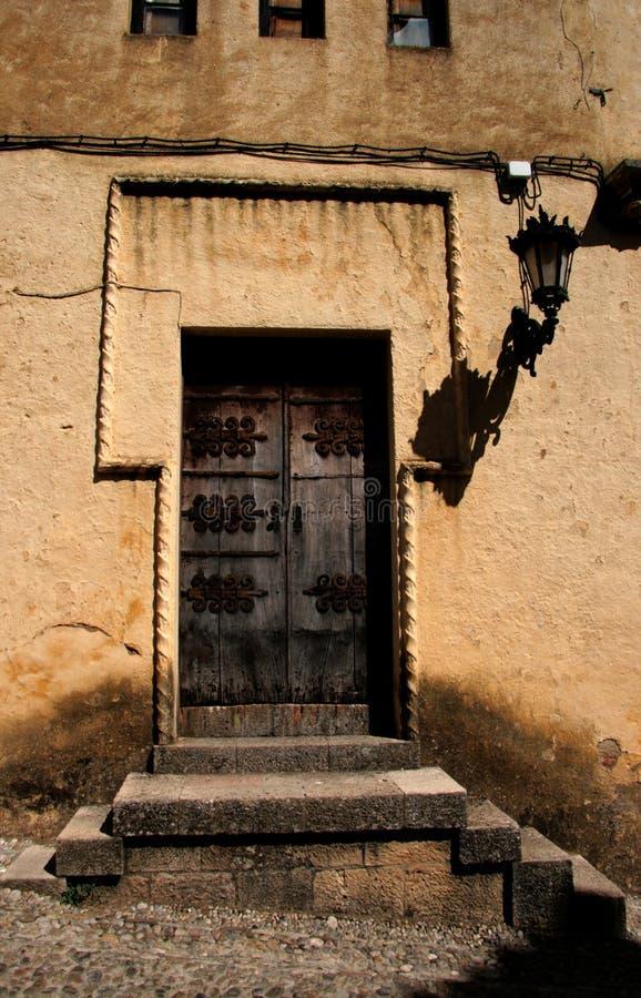Παλαιά, σκοτεινή πόρτα στον τοίχο πετρών του μεσαιωνικού σπιτιού στοκ εικόνα