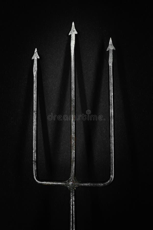 Παλαιά, σκουριασμένη και τρίαινα μετάλλων που πετά τη σκιά στη μαύρη επιφάνεια υποβάθρου στοκ φωτογραφία