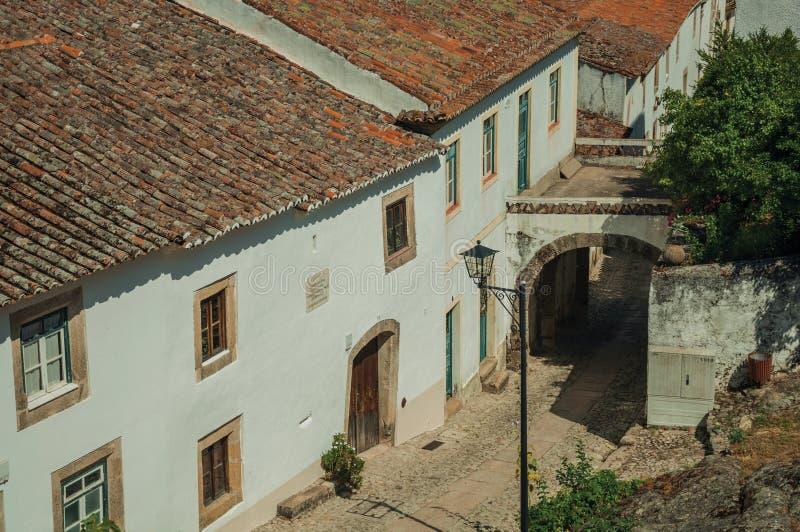 Παλαιά σπίτια στην αλέα και το πέρασμα κυβόλινθων κάτω από την αψίδα στοκ εικόνα με δικαίωμα ελεύθερης χρήσης