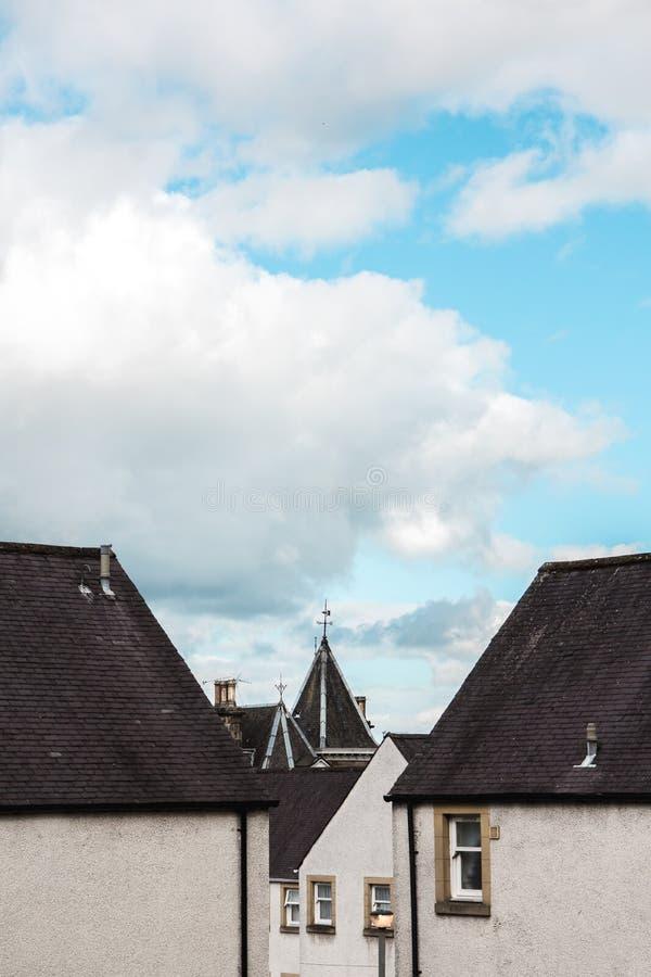 Παλαιά σπίτια χωρών στο χωριό, Σκωτία κάτω από έναν φωτεινό μπλε ουρανό κιρκιριών στοκ εικόνα με δικαίωμα ελεύθερης χρήσης