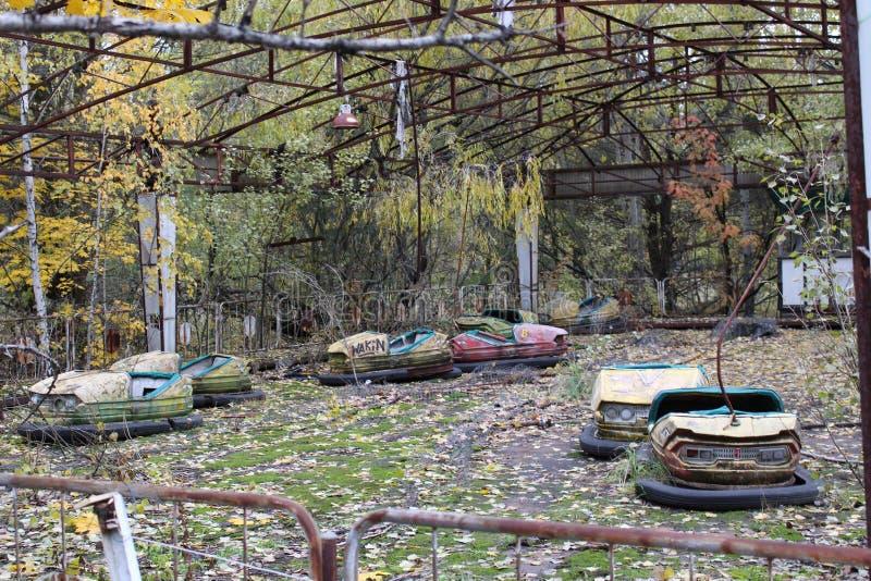 Παλαιά σπασμένα σκουριασμένα ραδιενεργά κίτρινα αυτοκίνητα μετάλλων, ηλεκτρικά αυτοκίνητα των παιδιών, που εγκαταλείπονται μεταξύ στοκ φωτογραφία