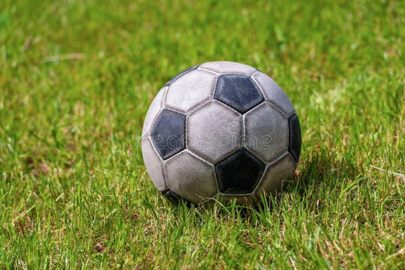 Παλαιά σφαίρα ποδοσφαίρου δέρματος στον αθλητισμό ποδοσφαίρου χλόης στοκ φωτογραφίες