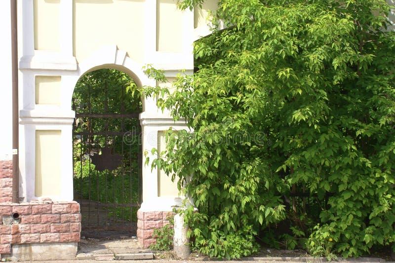 Παλαιά σχηματισμένη αψίδα μετάβαση σε έναν τουβλότοιχο μεταξύ των πράσινων δέντρων στοκ φωτογραφίες με δικαίωμα ελεύθερης χρήσης