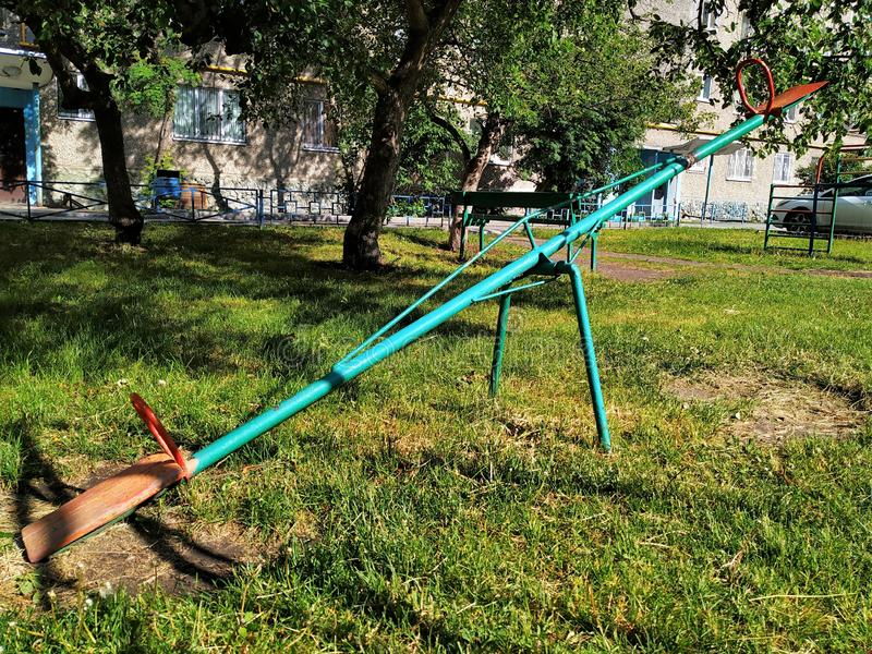 Παλαιά ταλάντευση σιδήρου στην παιδική χαρά Ηλιόλουστη θερινή ημέρα Ο εξοπλισμός είναι μπλε με τα κόκκινα καθίσματα στοκ εικόνα με δικαίωμα ελεύθερης χρήσης