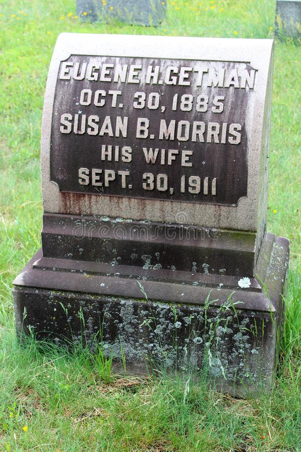 Παλαιά χαρασμένη ταφόπετρα που τίθεται μεταξύ άλλων ταφοπετρών και της πράσινης χλόης, νεκροταφείο Greenridge, Saratoga Springs,  στοκ εικόνες
