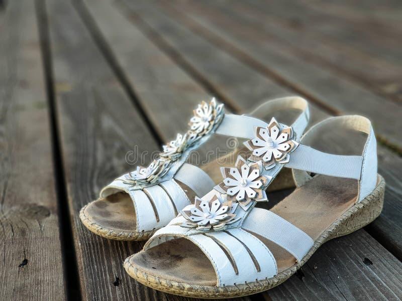 Παλαιά χρησιμοποιημένα άσπρα παπούτσια/σανδάλια ξύλινα floorboards στοκ φωτογραφία