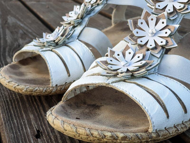 Παλαιά χρησιμοποιημένα άσπρα παπούτσια/σανδάλια ξύλινα floorboards στοκ εικόνα με δικαίωμα ελεύθερης χρήσης