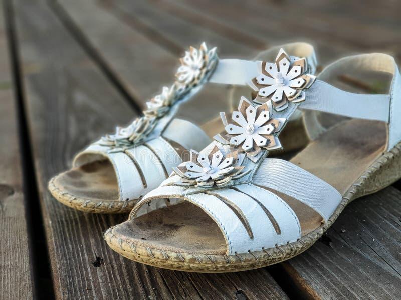 Παλαιά χρησιμοποιημένα άσπρα παπούτσια/σανδάλια ξύλινα floorboards στοκ φωτογραφία με δικαίωμα ελεύθερης χρήσης