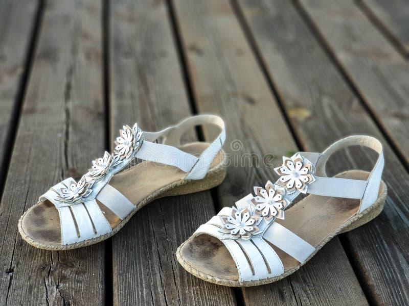 Παλαιά χρησιμοποιημένα άσπρα παπούτσια/σανδάλια ξύλινα floorboards στοκ εικόνες