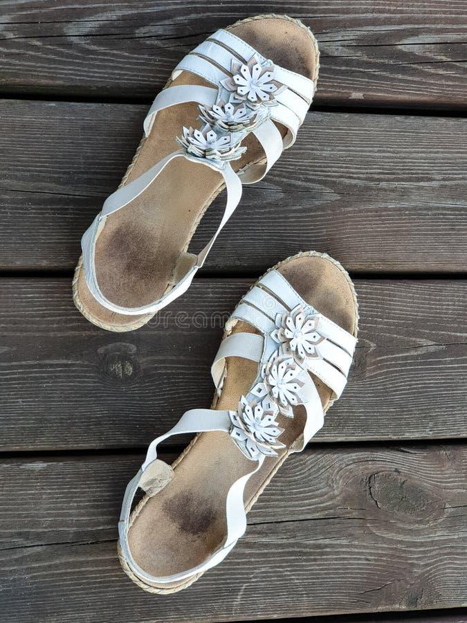 Παλαιά χρησιμοποιημένα άσπρα παπούτσια/σανδάλια ξύλινα floorboards στοκ εικόνες με δικαίωμα ελεύθερης χρήσης