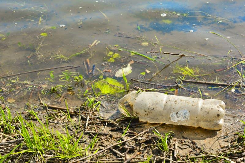 Παλαιά χρησιμοποιημένα πλαστικά μπουκάλια στον ποταμό Μολυσμένες όχθεις του ποταμού Πλαστικά μπουκάλια και απορρίμματα στο νερό Π στοκ φωτογραφία