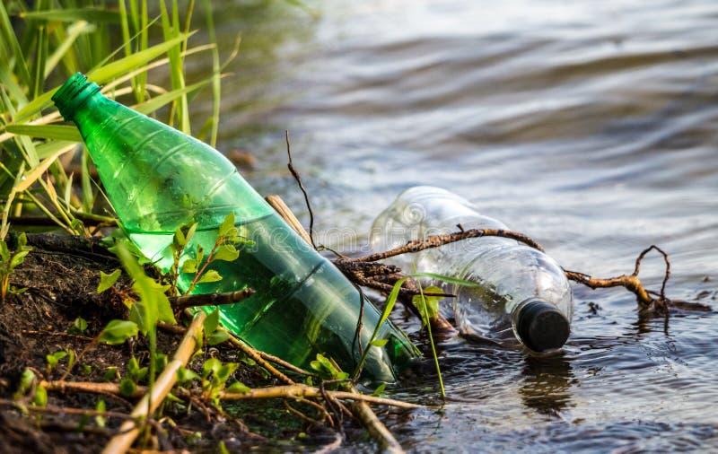 Παλαιά χρησιμοποιημένα πλαστικά μπουκάλια στο ποτάμι Μισισιπή στοκ εικόνα