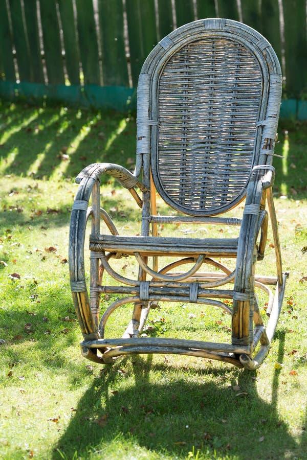 Παλαιά ψάθινη λικνίζοντας καρέκλα στον κήπο στοκ εικόνα