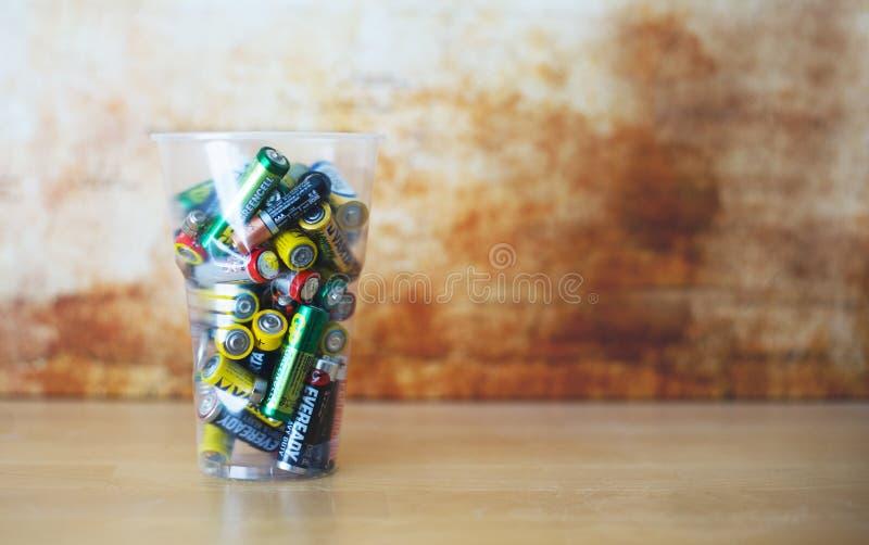 Παλαιές κενές μη επαναφορτιζόμενες μπαταρίες Pilled επάνω στο πλαστικό φλυτζάνι ανασκόπηση που θολώνεται αφηρημένη στοκ εικόνες με δικαίωμα ελεύθερης χρήσης