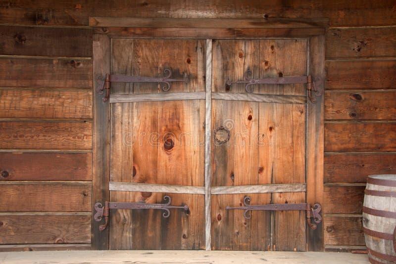Παλαιές ξύλινες διπλές πόρτες με το σκουριασμένο ξεπερασμένο υλικό, στοκ εικόνες με δικαίωμα ελεύθερης χρήσης