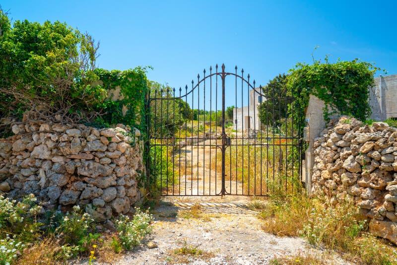 Παλαιές πύλες μετάλλων με το φράκτη βράχου γύρω από το έδαφος στοκ φωτογραφία με δικαίωμα ελεύθερης χρήσης