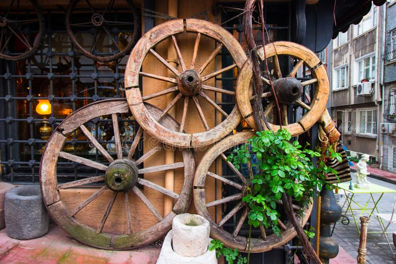 Παλαιές ρόδες κάρρων, διακοσμημένος τοίχος με τις ρόδες, παλαιό ShopWall στοκ φωτογραφία