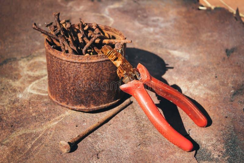 Παλαιές σκουριασμένες σπασμένες εργαλεία, καρφιά και πένσες σε ένα υπόβαθρο της σκουριάς στοκ εικόνα