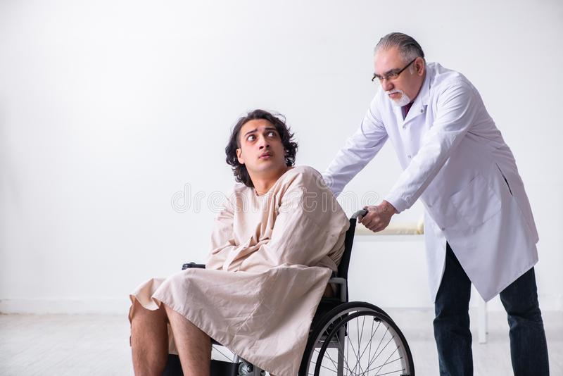 Παλαιοί αρσενικοί ψυχίατρος και ασθενής γιατρών στην αναπηρική καρέκλα στοκ εικόνα με δικαίωμα ελεύθερης χρήσης