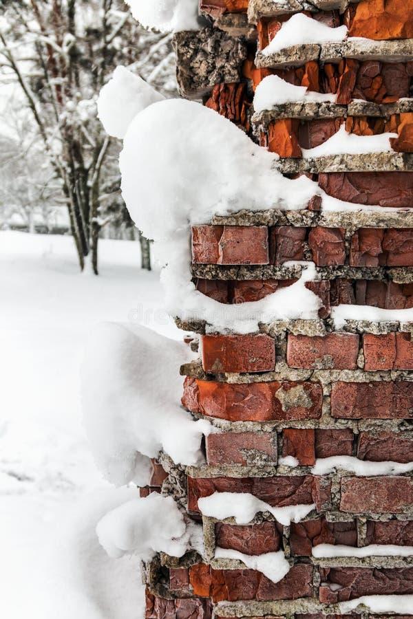 Παλαιοί και σπασμένοι παγωμένοι τουβλότοιχοι στο χιόνι και τον πάγο στοκ εικόνες
