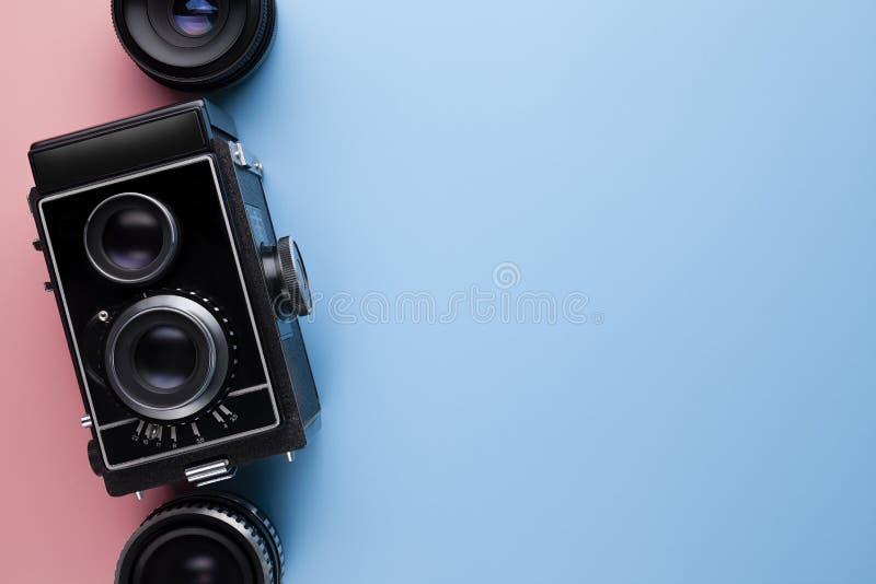 Παλαιοί κλασικοί κάμερα και φακός στο ρόδινο και μπλε υπόβαθρο κρητιδογραφιών στοκ εικόνες