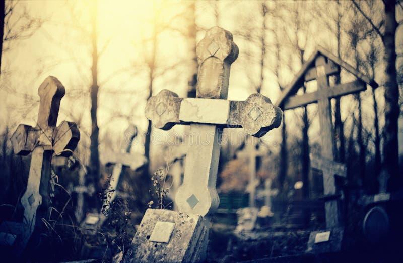Παλαιοί lop-sided επιτάφιοι σταυροί στο νεκροταφείο το βράδυ στοκ εικόνα