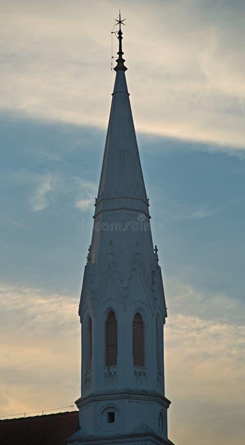 Παλαιός άσπρος πύργος κουδουνιών μιας Προτεσταντικής Εκκλησίας ενάντια στο νεφελώδη ουρανό στοκ φωτογραφίες