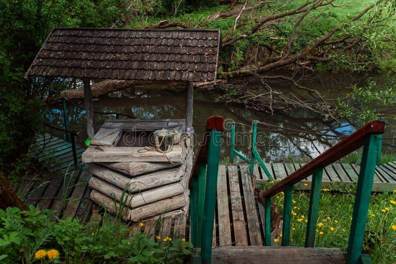 Παλαιός αγροτικός ξύλινος καλά στον ποταμό στοκ φωτογραφία με δικαίωμα ελεύθερης χρήσης
