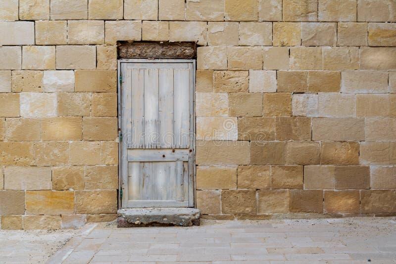 Παλαιός εγκαταλειμμένος τοίχος τούβλων πετρών με τη σπασμένη ξεπερασμένη ξύλινη πόρτα στοκ φωτογραφίες
