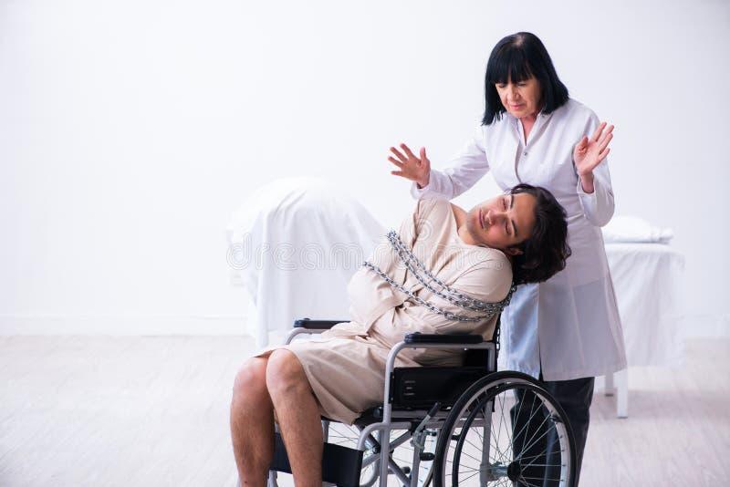 Παλαιός θηλυκός ψυχίατρος που επισκέπτεται το νέο αρσενικό ασθενή στοκ εικόνα