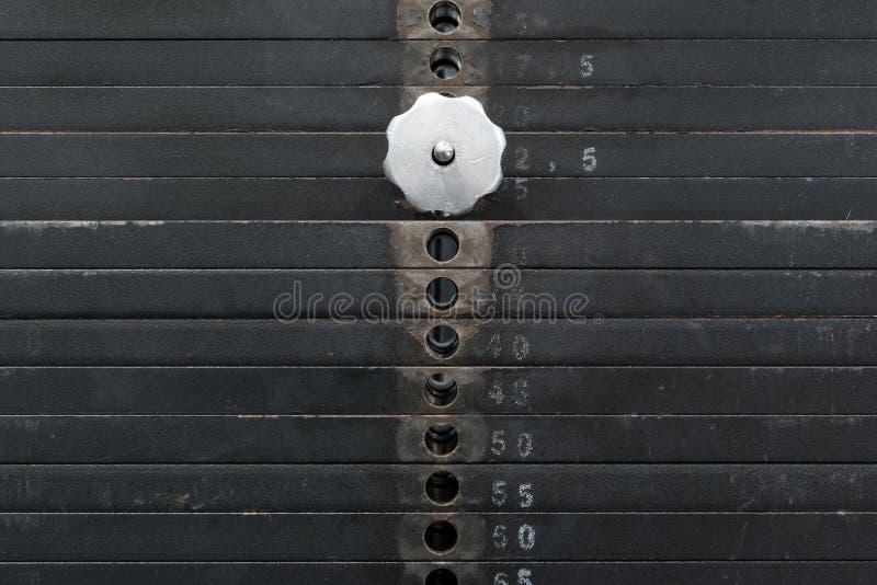 Παλαιός και χρησιμοποιημένος μαύρος σωρός βάρους με τους άσπρους αριθμούς σε μια γυμναστική Σκουριασμένα επίπεδα βάρη μετάλλων στοκ φωτογραφία