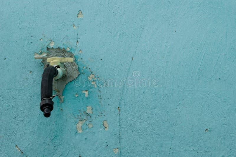 Παλαιός κρουνός στο υπόβαθρο ενός παλαιού μπλε τοίχου με τις ρωγμές στοκ εικόνες