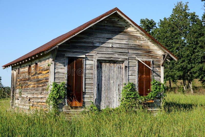 Παλαιός λίγο ξύλινο κτήριο με τη σκουριασμένη στέγη μετάλλων στοκ φωτογραφία με δικαίωμα ελεύθερης χρήσης