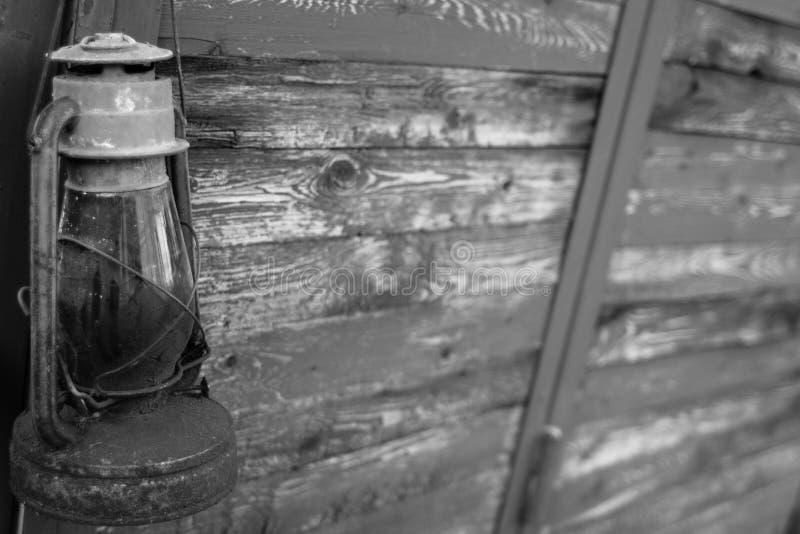 Παλαιός λαμπτήρας κηροζίνης σε ένα ξύλινο υπόβαθρο στη γραπτή εικόνα στοκ εικόνα με δικαίωμα ελεύθερης χρήσης