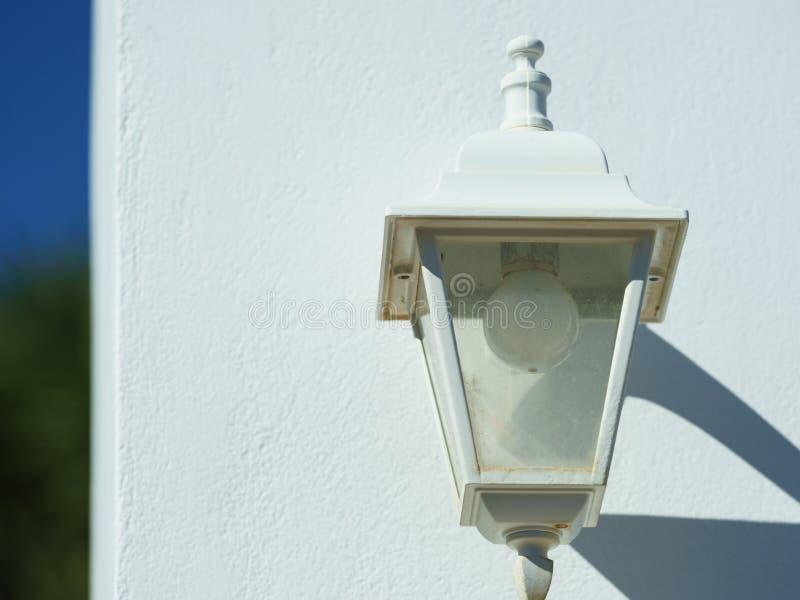 Παλαιός λαμπτήρας στον καφετή άσπρο τοίχο στοκ φωτογραφίες