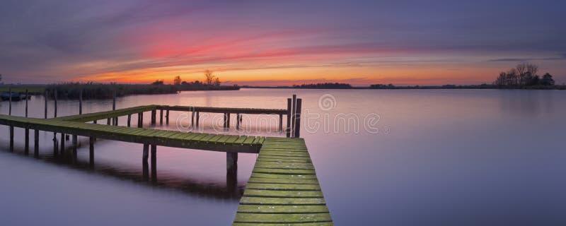 Παλαιός λιμενοβραχίονας σε μια λίμνη στο ηλιοβασίλεμα στοκ εικόνες