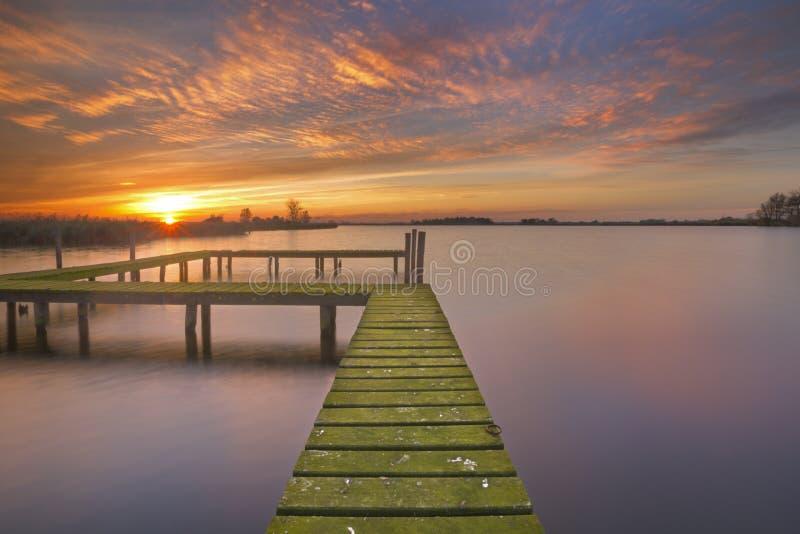 Παλαιός λιμενοβραχίονας σε μια λίμνη στο ηλιοβασίλεμα στοκ εικόνα