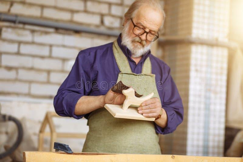 Παλαιός ξυλουργός που εργάζεται με το glasspaper στοκ εικόνες