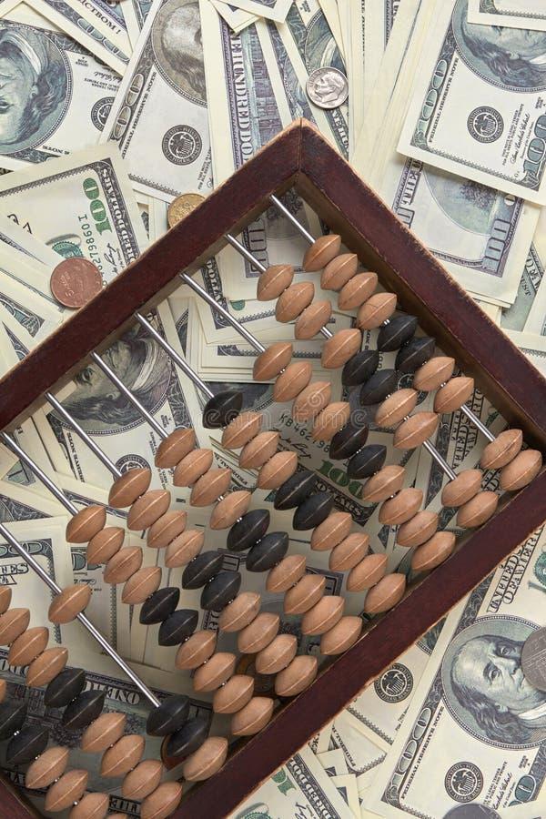 Παλαιός ξύλινος άβακας λογιστικής στο σωρό των χρημάτων στοκ εικόνες