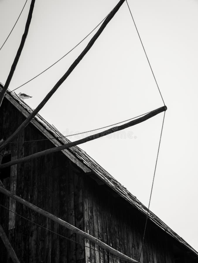 Παλαιός ξύλινος ανεμόμυλος στο υπόβαθρο του μπλε ουρανού στοκ φωτογραφίες