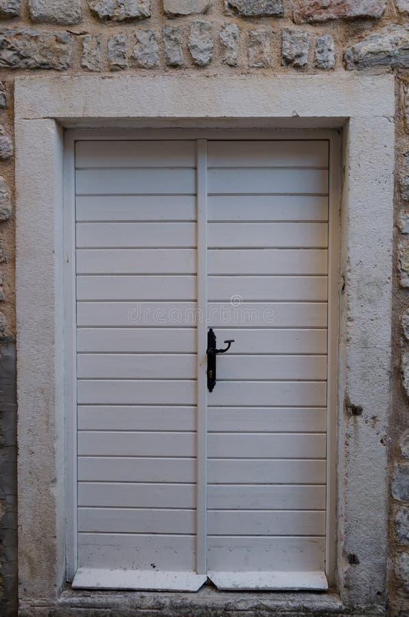 Παλαιός ξύλινος, λευκό η πόρτα που κλείνουν στο μπουλόνι σιδήρου στοκ εικόνες