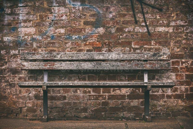 Παλαιός ξύλινος πάγκος ενάντια σε έναν τουβλότοιχο με τα γκράφιτι στοκ φωτογραφίες