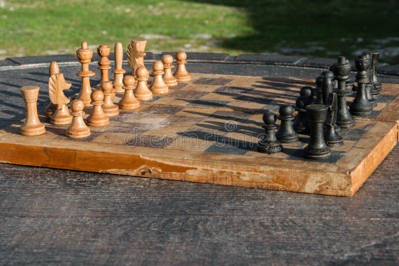 Παλαιός ξύλινος πίνακας σκακιού σε μια ξύλινη επιτραπέζια υπαίθρια, στρατηγική δραστηριότητα υπαίθρια στοκ φωτογραφίες με δικαίωμα ελεύθερης χρήσης