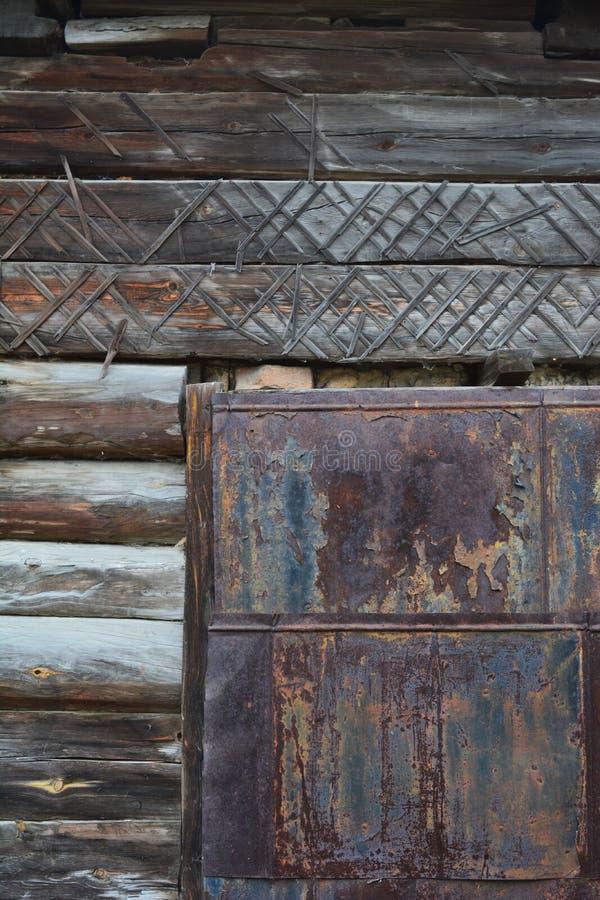 Παλαιός ξύλινος τοίχος με τη σκουριασμένη πόρτα μετάλλων Τεμάχιο της πρόσοψης ενός σπιτιού κούτσουρων που χτίζεται στο τέλος του  στοκ φωτογραφία