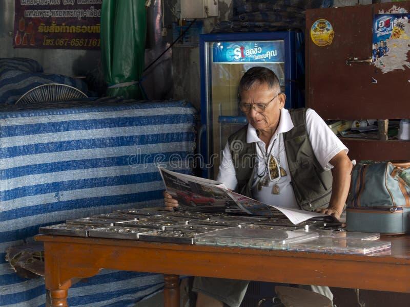 Παλαιός πωλητής γοητειών που διαβάζει μια εφημερίδα στην αγορά στοκ εικόνες