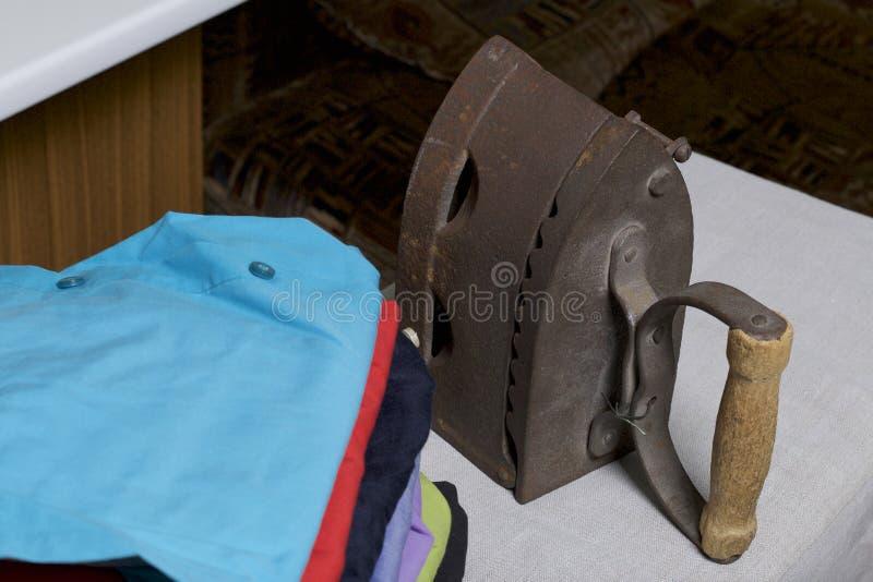 Παλαιός σίδηρος, που θερμαίνεται από τους καυτούς άνθρακες Τοποθετημένος στο ύφασμα λινού Στάση σε έναν σιδερώνοντας πίνακα Εκτός στοκ φωτογραφίες