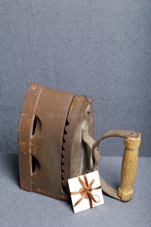 Παλαιός σίδηρος, που θερμαίνεται από τους καυτούς άνθρακες Τοποθετημένος στο γκρίζο ύφασμα Εδώ κοντά μια ευχετήρια κάρτα στοκ εικόνα με δικαίωμα ελεύθερης χρήσης