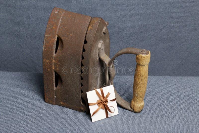 Παλαιός σίδηρος, που θερμαίνεται από τους καυτούς άνθρακες Τοποθετημένος στο γκρίζο ύφασμα Εδώ κοντά μια ευχετήρια κάρτα στοκ φωτογραφίες